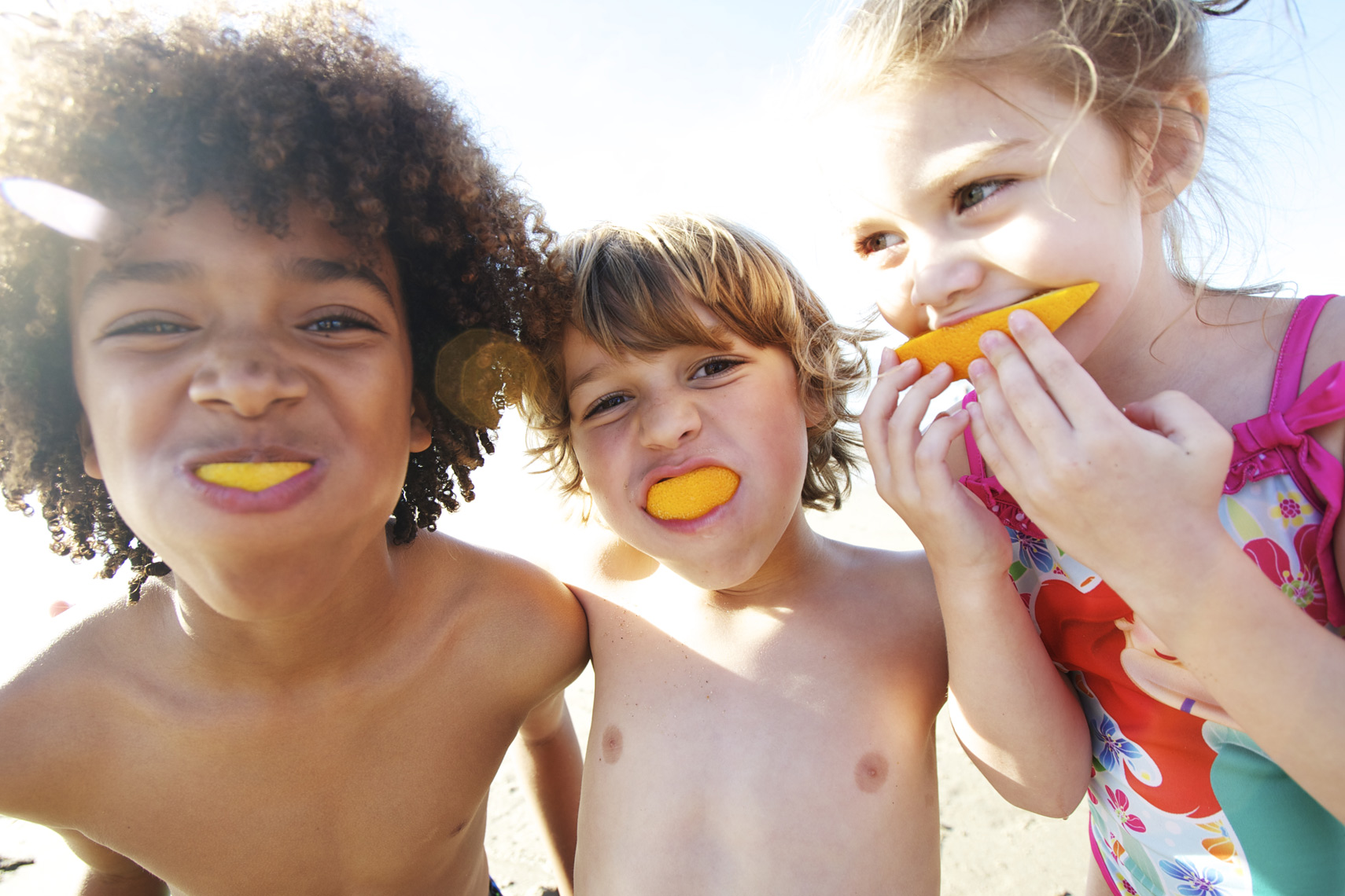 Kids enjoying orange slices as smiles/ Steve Mason Photography